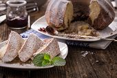 stock photo of pound cake  - ring cake sprinkled with sugar on old wooden table - JPG