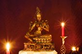 foto of altar  - Golden Indian statue of compassion from Hinduism tradition on altar and lit candles - JPG
