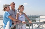 stock photo of granddaughter  - Grandfather with grandson and granddaughter admire the city view from the roof - JPG