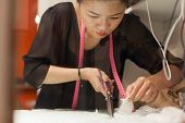 stock photo of tailoring  - Asian woman tailor fashion clothes dress designer working with scissors fabric on table  - JPG