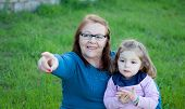 picture of granddaughter  - Proud grandmother with her granddaughter sitting on the grass in the field - JPG