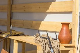 image of trident  - gladiatorial net and trident on a wooden bench - JPG