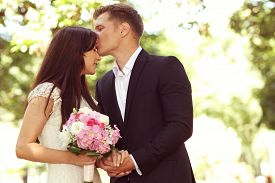 image of forehead  - Capture of Groom kissing his bride on forehead - JPG