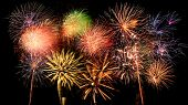 stock photo of firework display  - Bright and colorful fireworks against a black night sky - JPG