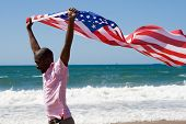 stock photo of waving american flag  - young african american man waving a USA flag on beach - JPG