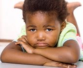 picture of sad eyes  - african american little girl lying on floor - JPG