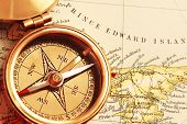Antique brass compass over old Canadian map background