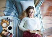 Young beautiful blonde woman with cup of coffee lying down home relaxing by the window reading book. poster