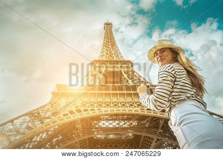 poster of Woman tourist selfie near the Eiffel Tower in Paris under sunlight and blue sky. Famous popular tour