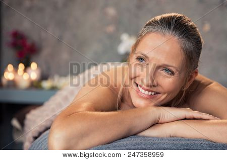 poster of Closeup of a blonde woman in a wellness center for massage therapy. Portrait of a beautiful mature w