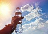 A Bottle Of Water In A Hand Against The Sky And Sun. Drinking Water. Drinking Water At Dawn. Drinkin poster