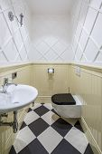 Restroom In A Classic Style With Textured White And Beige Walls And Chess Tiles On The Floor. There  poster
