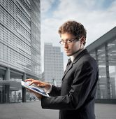 stock photo of tablet pc computer  - Businessman using a tablet pc with office buildings in the background - JPG