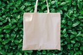 Blank White Mockup Linen Cotton Tote Bag On Green Bush Trees Foliage Background. Eco Nature Friendly poster