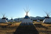 stock photo of teepee  - Colorful teepees set up in a circle with the Rocky Mountains in the background