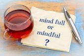 Mind full or mindful   Inspiraitonal handwriting on a napkin with a cup of tea. poster