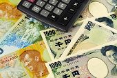 foto of nzd  - New Zealand and Japanese currency pair commonly used in forex trading with calculator - JPG
