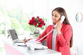 Beauty Salon Receptionist Talking On Phone At Desk poster