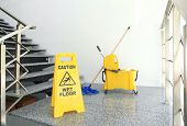 Safety Sign With Phrase caution Wet Floor And Mop Bucket On Stairs. Cleaning Tools poster