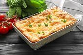 Baking tray with tasty spinach lasagna on wooden table poster