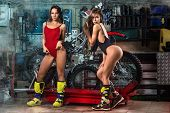 Two Sexy Model Girls In Lingerie Posing With Tools Repairing Motorcycle Using Tools In Garage poster