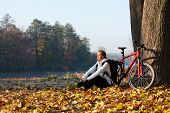 pic of peppy  - Peppy woman cyclist with bike sits among fallen leaves autumn morning in nature illuminated by the rays of the rising sun - JPG