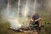 Holiday Camp. Man Traveler Roast Sausages On Stick On Campfire In Forest. Summer Camping, Hiking, Va poster