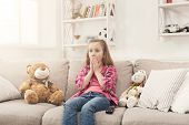 Shocked Little Casual Girl Watching Tv. Frightened Female Kid Sitting On Sofa, Home Alone, Watching  poster