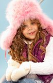 Happy girl in pink furry hat with snow in hands looking at camera poster
