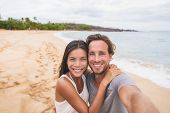 Two friends taking self portrait picture with phone. Smiling young interracial couple taking selfie  poster