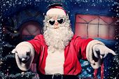 stock photo of nicholas  - Santa Claus is listening to music in headphones - JPG