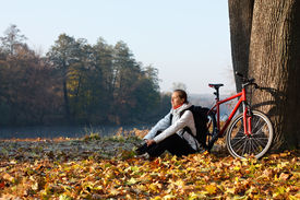picture of peppy  - Peppy woman cyclist with bike sits among fallen leaves autumn morning in nature illuminated by the rays of the rising sun - JPG