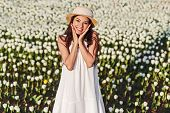 Lovely Romantic Happy Young Female In White Sundress And Hat Looking At Camera While Standing On Fie poster