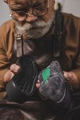 Senior, Bearded Cobbler Holding Shoe And Sole In Workshop poster
