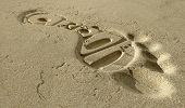 foto of carbon-footprint  - A footprint in some beach sand with the tread shape spelling out the word carbon - JPG