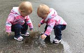 stock photo of identical twin girls  - One year old twin girls playing with a puddle of water - JPG