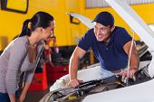 trustworthy auto technician talking to female customer in garage