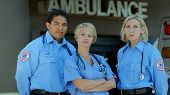 stock photo of paramedic  - Three paramedics stand outside an ambulance and emergency room - JPG