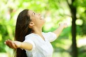 picture of praises  - Attractive young woman rejoicing in a spring or summer garden standing sideways with her arms outstretched and her head raised to the heavens enjoying the freshness and beauty of nature - JPG