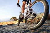 stock photo of exercise bike  - Extreme mountain bike sport athlete man riding outdoors lifestyle trail - JPG
