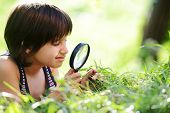 stock photo of muslim kids  - Happy kid exploring nature with magnifying glass - JPG