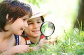 stock photo of cute kids  - Happy kid exploring nature with magnifying glass - JPG