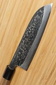 Japanese damascus carbon steel knife on wooden cutting board