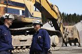 stock photo of jcb  - two site workers with giant bulldozer in the background - JPG