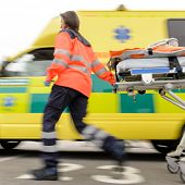stock photo of stretcher  - Running blurry paramedic woman rolling stretcher outside of ambulance car - JPG