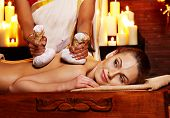 stock photo of panchakarma  - Woman having ayurvedic massage with pouch of rice - JPG