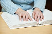 stock photo of handicap  - Blind or visually handicapped woman hands reading book written in Braille - JPG