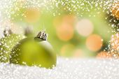 Beautiful Matt Green Christmas Ornaments on Snow Flakes Over an Abstract Snow and Light Background w