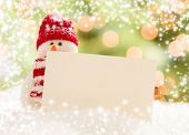 stock photo of snowmen  - Cute Snowman with Scarf and Hat Next To Blank White Card Over Abstract Snow and Light Background - JPG