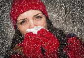 picture of blowing nose  - Sick Mixed Race Woman Wearing Winter Hat and Gloves Blowing Her Sore Nose with a Tissue in The Snow - JPG